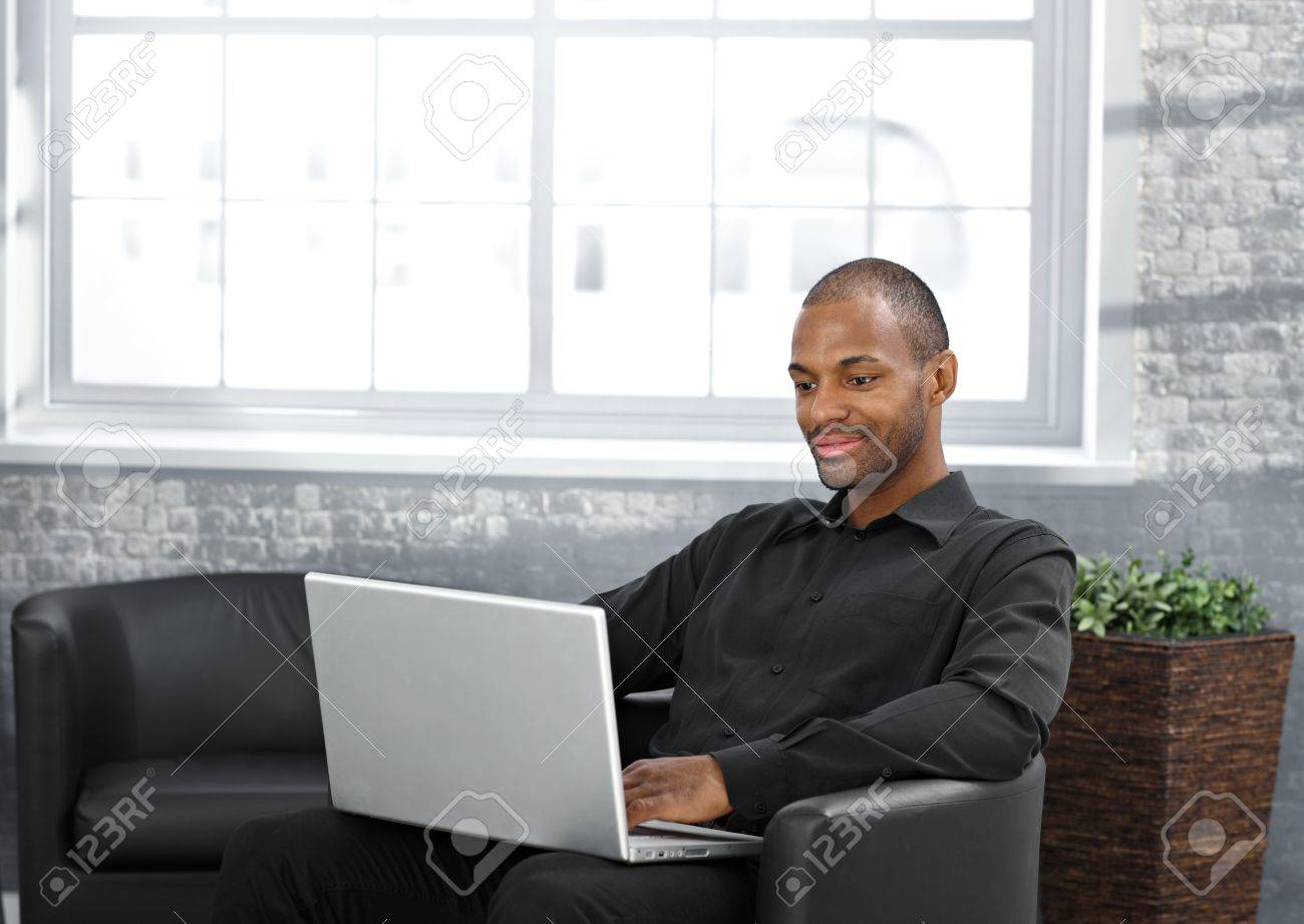 Businessman working on laptop computer, sitting in armchair in office lobby. Stock Photo - 12471545