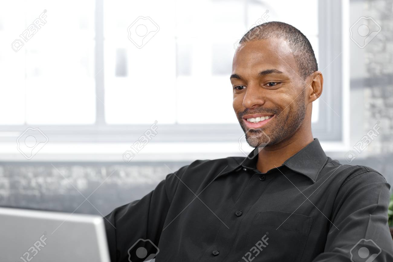 Happy handsome afro man using laptop computer, smiling, Stock Photo - 12471584