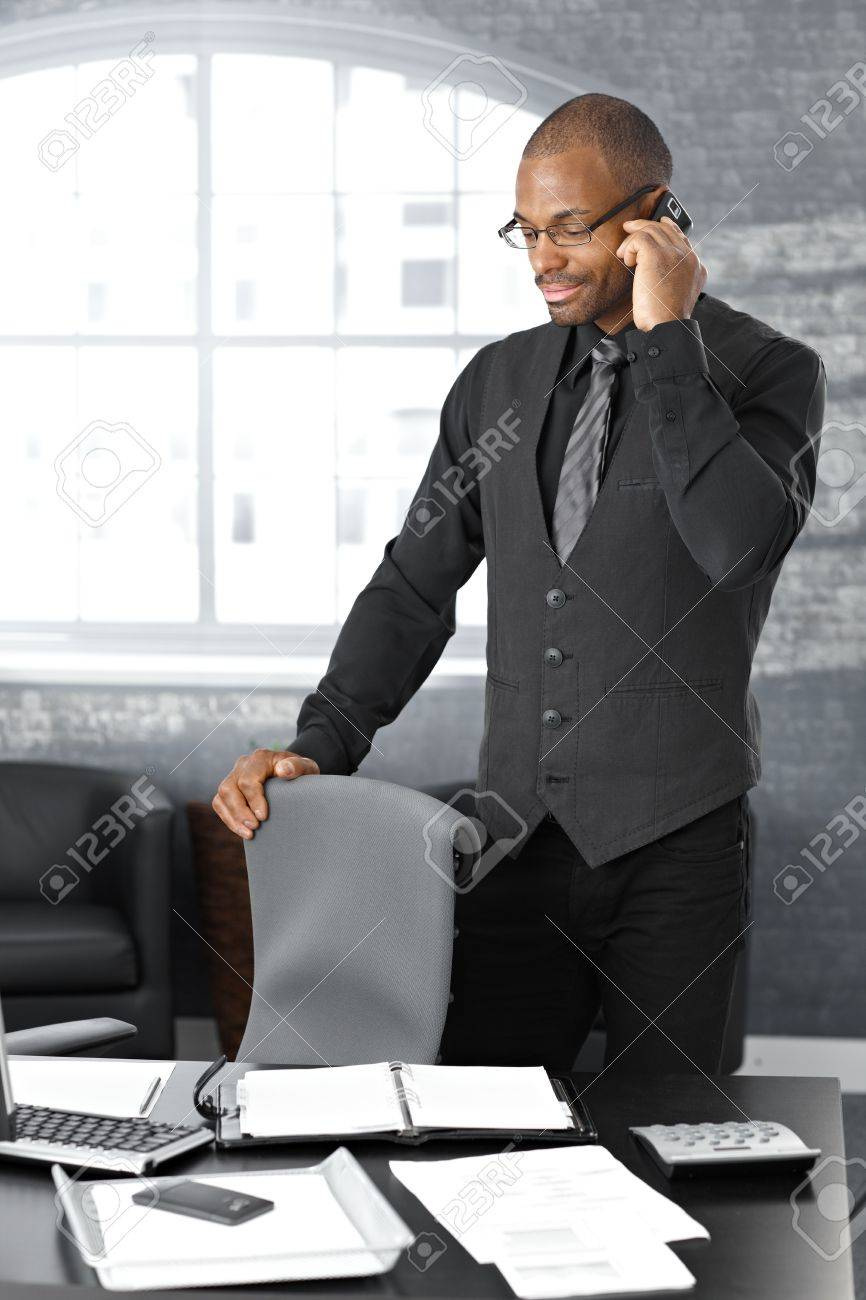 Businessman on mobile telephone call, standing at office desk, concentrating. Stock Photo - 12471600