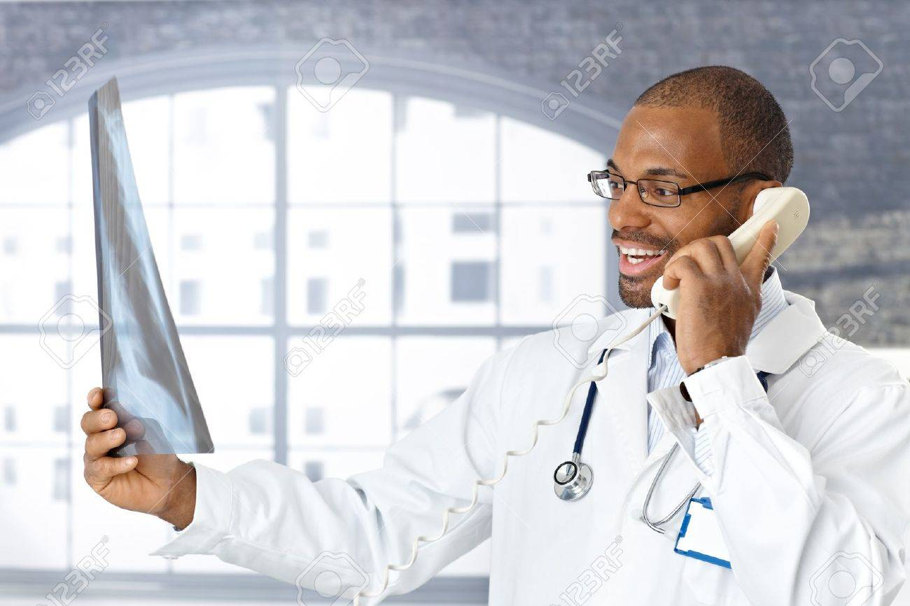 Doctor telling good news on phone, holding up x-ray image, smiling. Stock Photo - 12471585