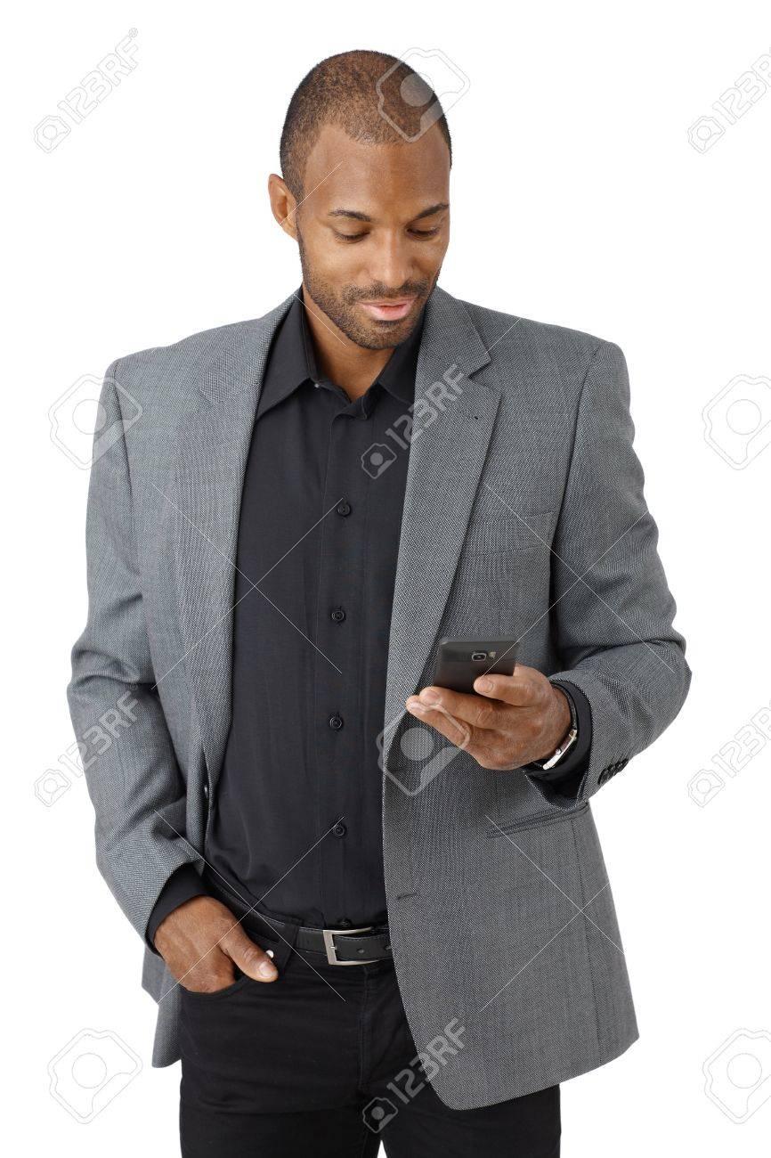 Handsome elegant ethnic businessman texting on mobile phone, smiling, cutout on white. Stock Photo - 12472121