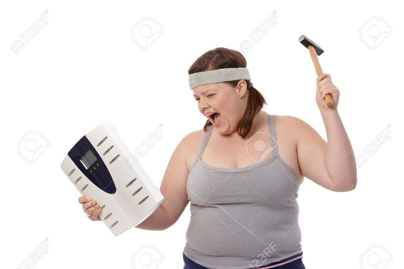 Angry fat woman punching scale by hammer, shouting. Stock Photo - 12472192