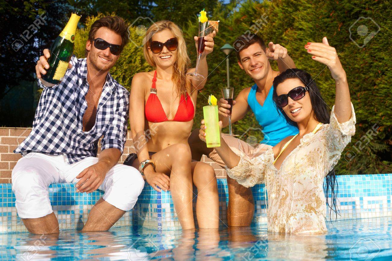 Cheerful young people sitting by swimming pool, drinking, having fun, enjoying holiday. Stock Photo - 12918710