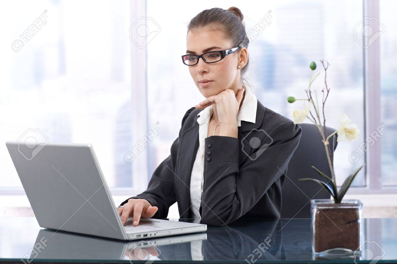 Smart businesswoman with glasses working on laptop computer at office table. Stock Photo - 13098524