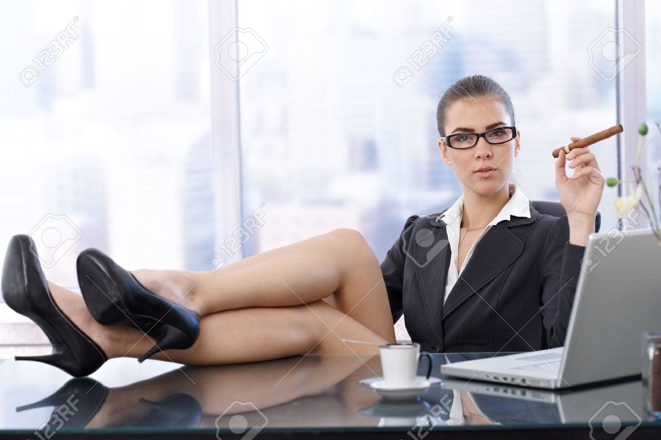 hot office pic. Hot Businesswoman Sitting With High Heels Feet Up On Office Desk, Holding Cigar, Looking Pic