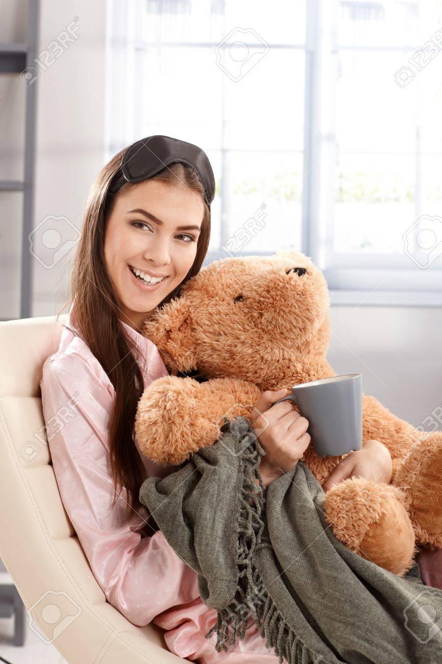 5c3499462a Foto de archivo - Mañana retrato de risa mujer abrazando con osito de  peluche y una manta en la casa