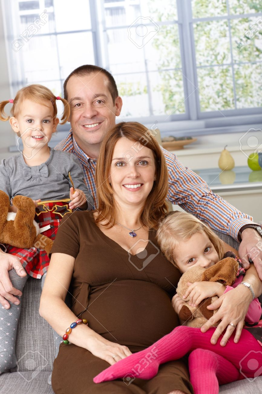 Portrait of happy family at home with father, pregnant mother and two daughters. Stock Photo - 13139219