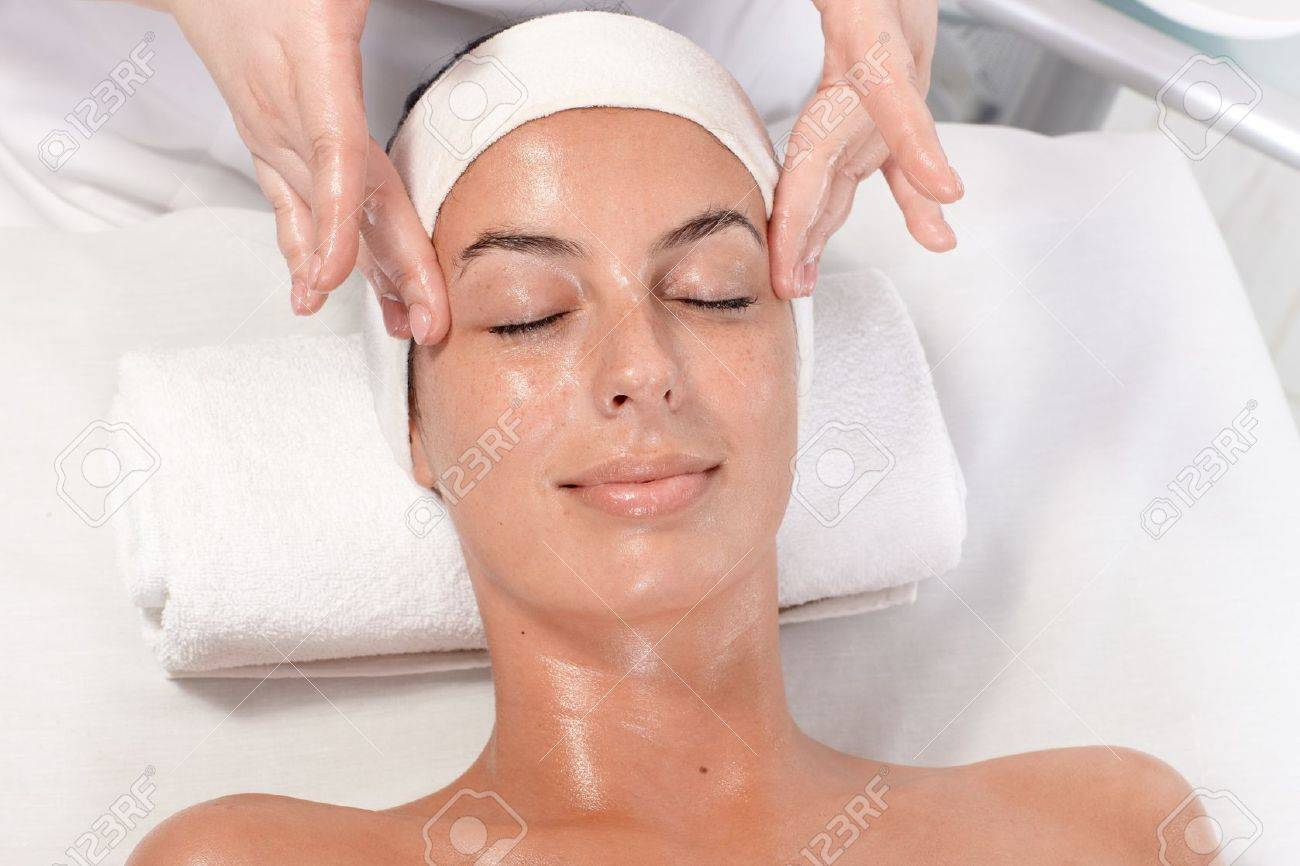 Young woman getting facial massage in beauty saloon, laying relaxed. Stock Photo - 13180310