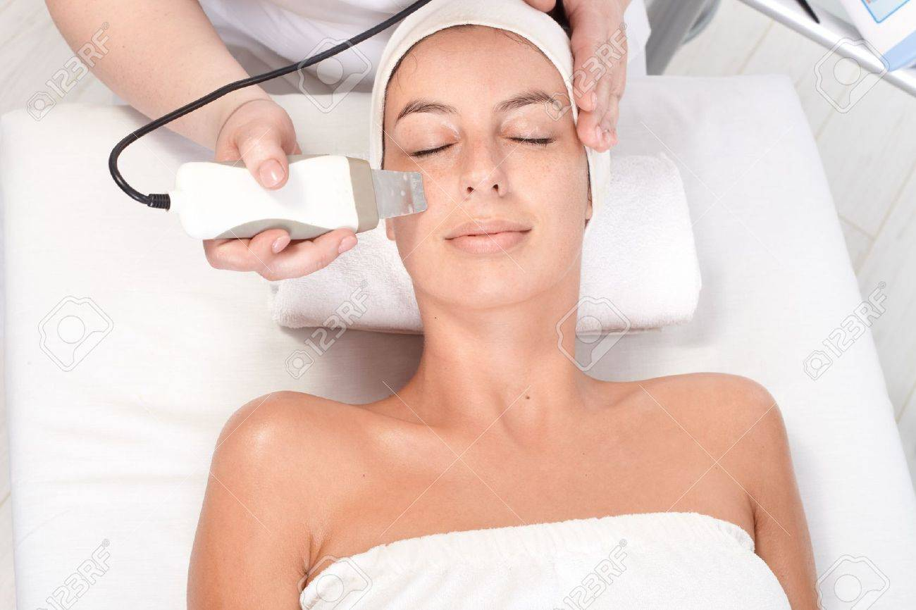 Young woman laying eyes closed, getting facial beauty treatment, view from above. Stock Photo - 13180295