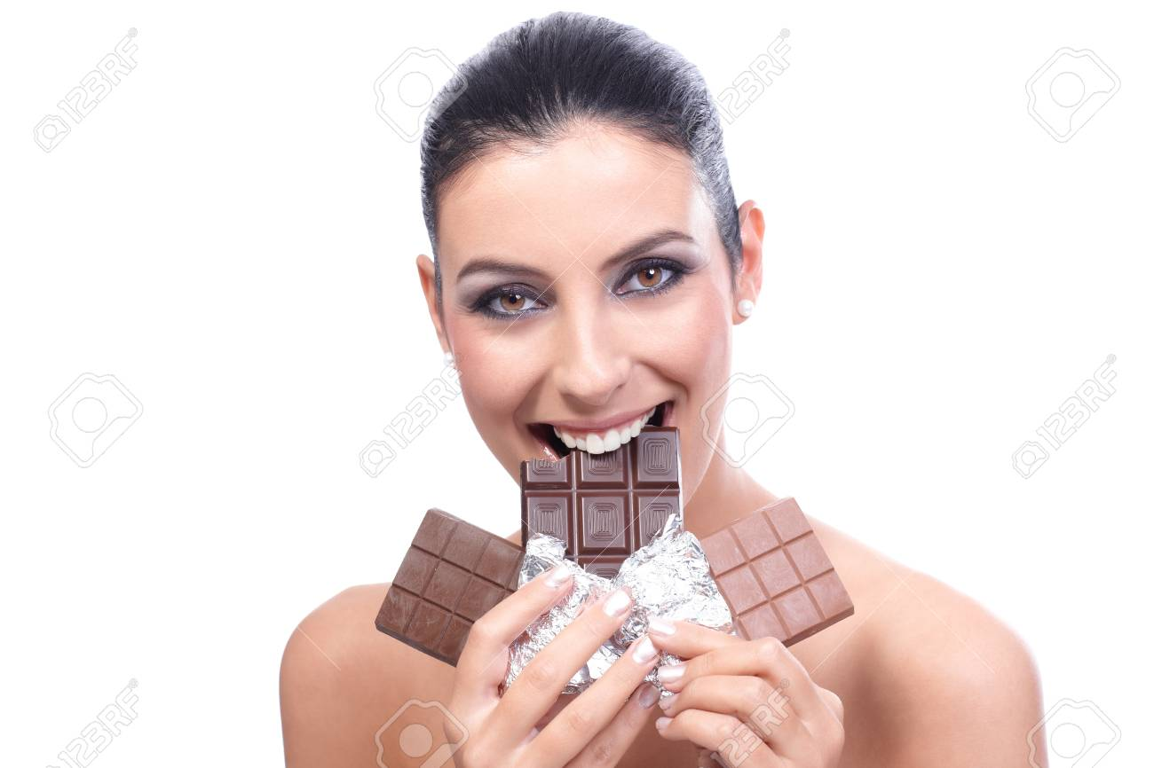 Attractive young woman holding several chocolate bars, biting one, smiling. Stock Photo - 13180159