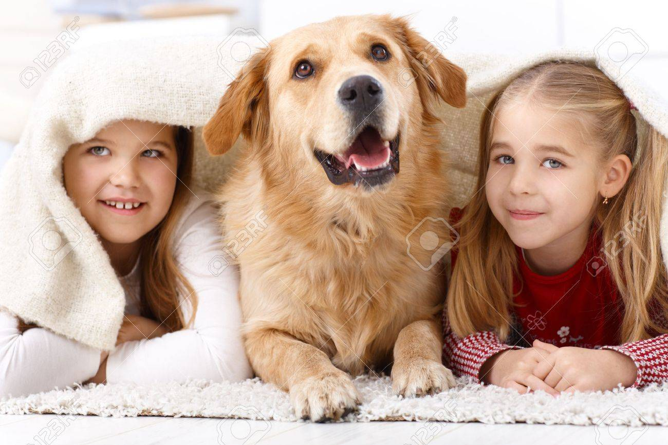 Little sisters and pet dog having fun at home, lying prone on floor, smiling under blanket. Stock Photo - 13250641