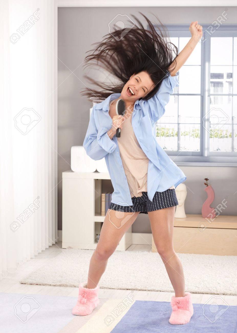 c3acf7ac132 Foto de archivo - Mujer joven feliz que actúa como estrella del pop, con  cepillo de pelo como micrófono, en pijama, el pelo largo volando en el aire.