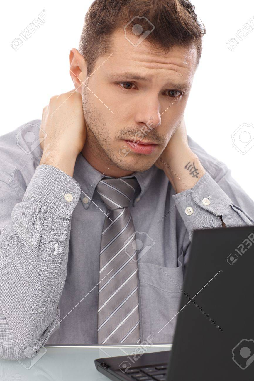 Tired, troubled businessman sitting at desk, working on laptop computer. Stock Photo - 13964904