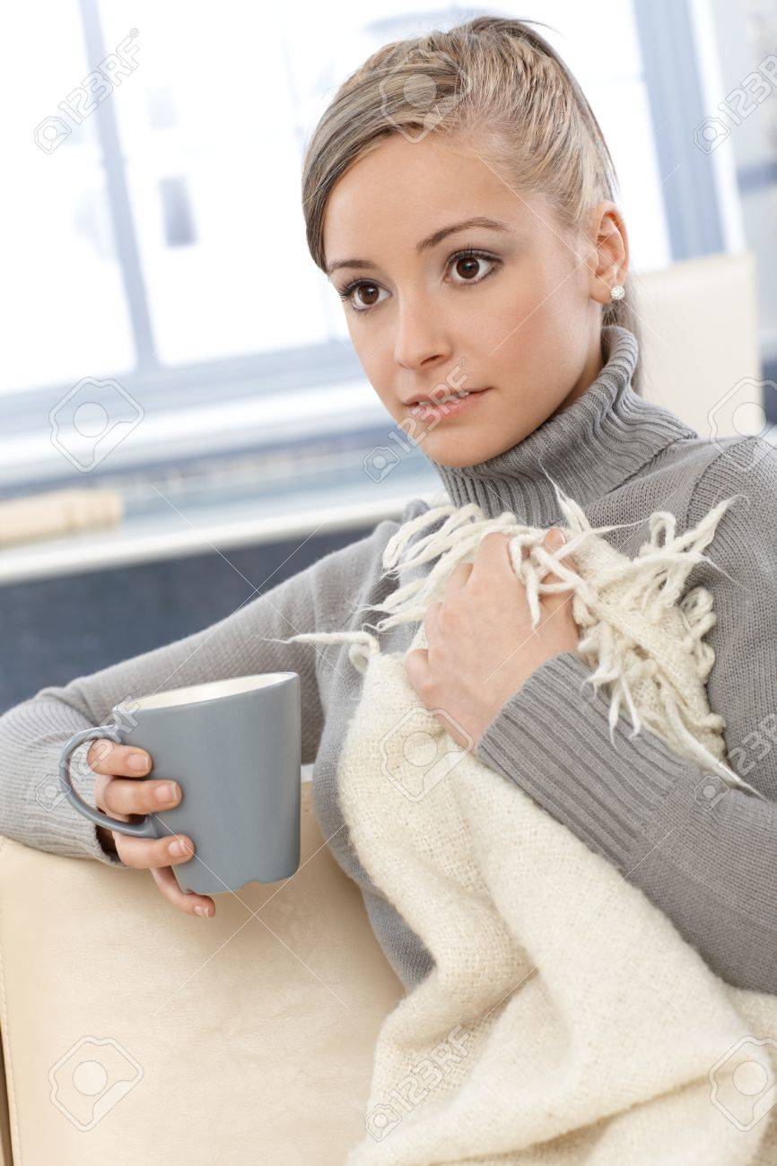 Young woman resting at home, drinking tea, covered by blanket. Stock Photo - 13964763