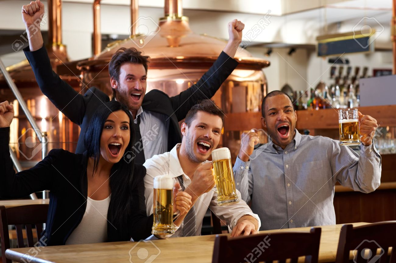Happy friends in pub watching sport in TV together drinking beer cheering for team and celebrating. Stock Photo - 13964770