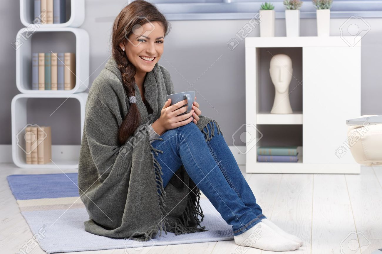 Winter portrait of happy girl laughing, cuddling with blanket and tea mug on living room floor. Stock Photo - 14427071