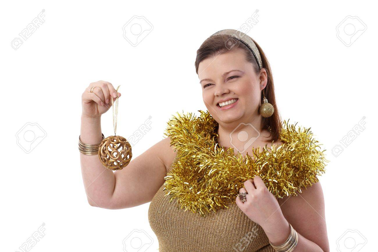 Happy plump woman holding christmas ornaments in hand, smiling. Stock Photo - 14426780