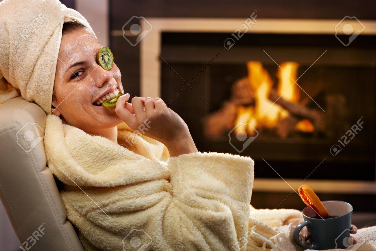 Funny woman eating fruit from kiwi facial mask, smiling, sitting in bathrobe in front of fireplace. Stock Photo - 14427623