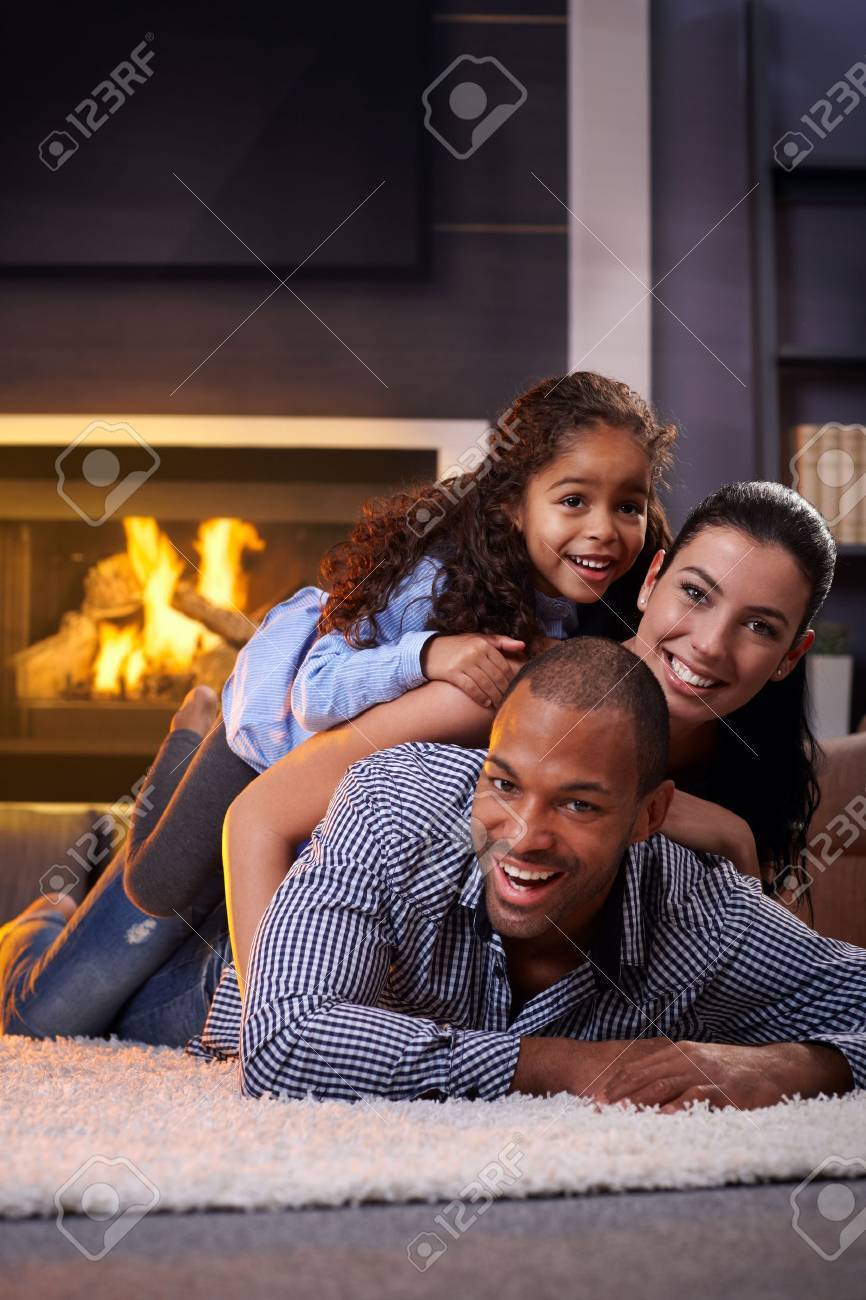 Happy interracial family having fun at home by fireplace, lying on each other's back, laughing. Stock Photo - 14427980