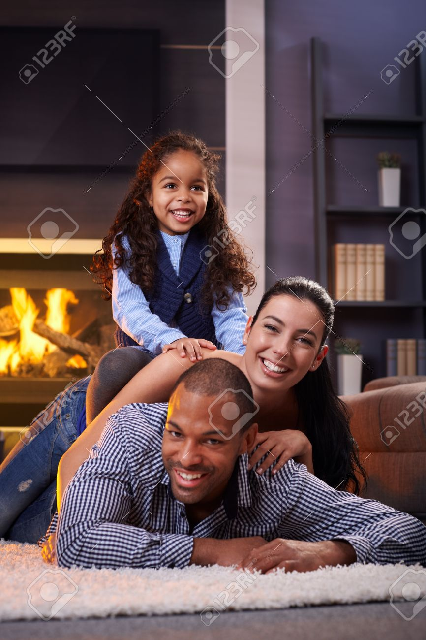Happy diverse family having fun at home on floor, lying on each other. Stock Photo - 14427973