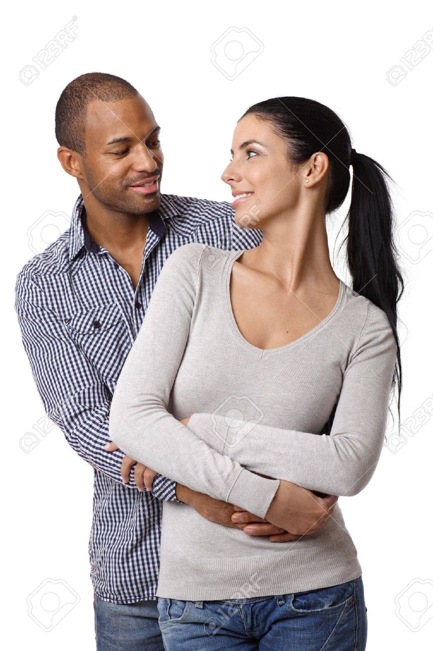 Diverse loving couple holding hands, embracing, smiling at each other. Stock Photo - 14428194