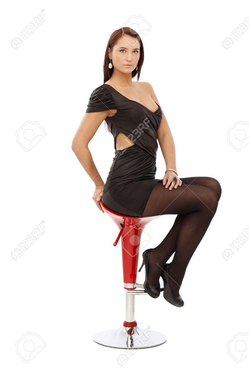 Pretty Woman In Sexy Black Mini Dress And High Heels Sitting