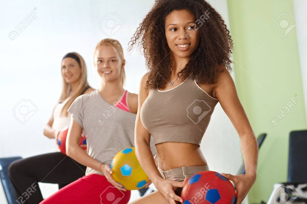 Beautiful afro woman exercising with ball at the gym, smiling. Stock Photo - 14746221