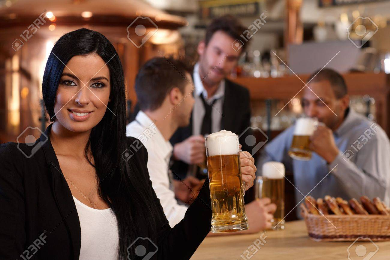 Portrait of beautiful young woman holding mug of beer in pub, looking at camera, smiling. Friends drinking in background. Stock Photo - 14821342
