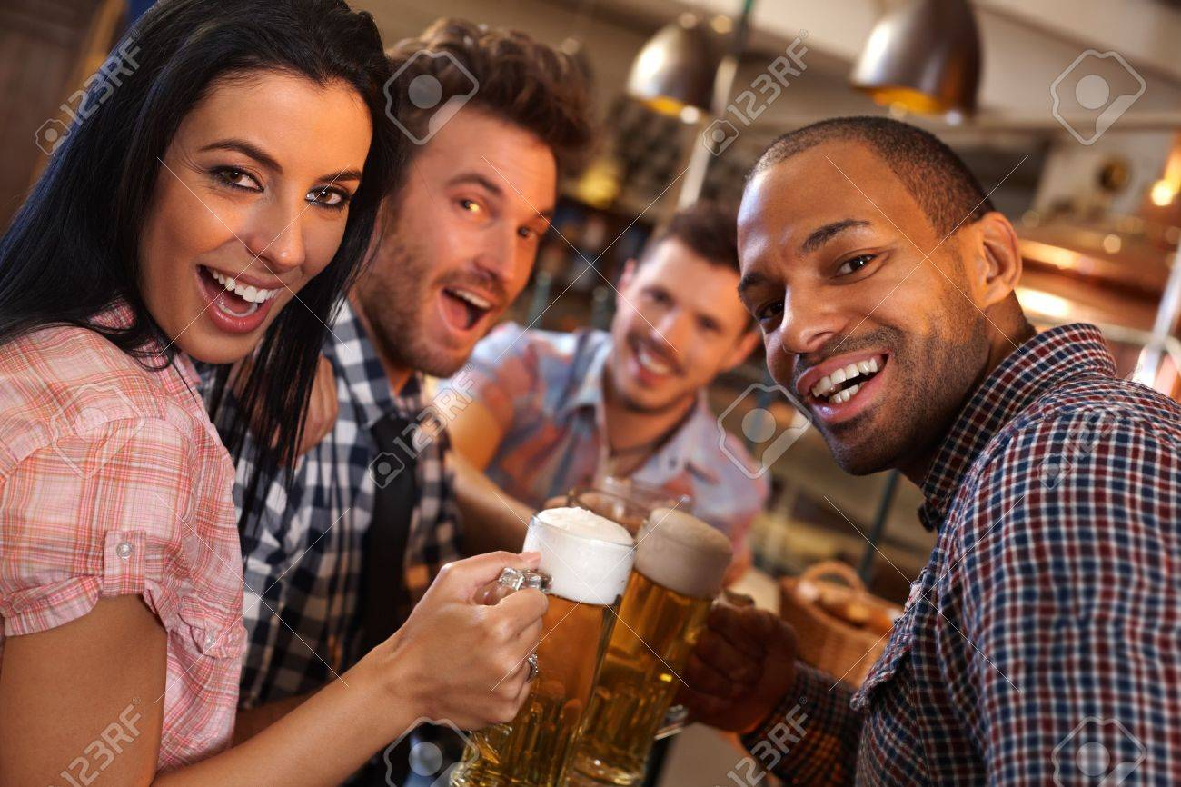 Group of happy young people drinking beer, having fun in pub, laughing. Stock Photo - 14821374