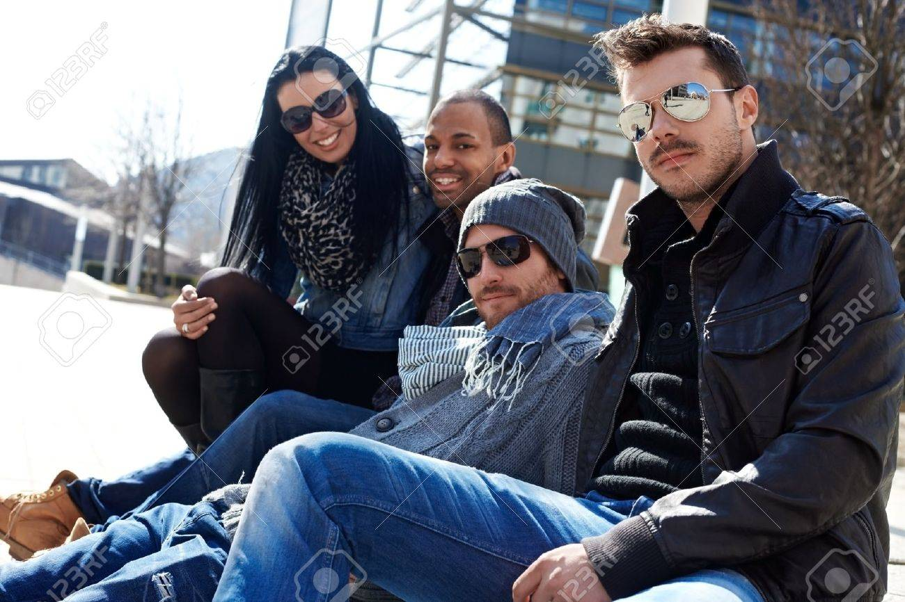 Group of trendy young people sitting outside of building, enjoying springtime sunshine Stock Photo - 14808425