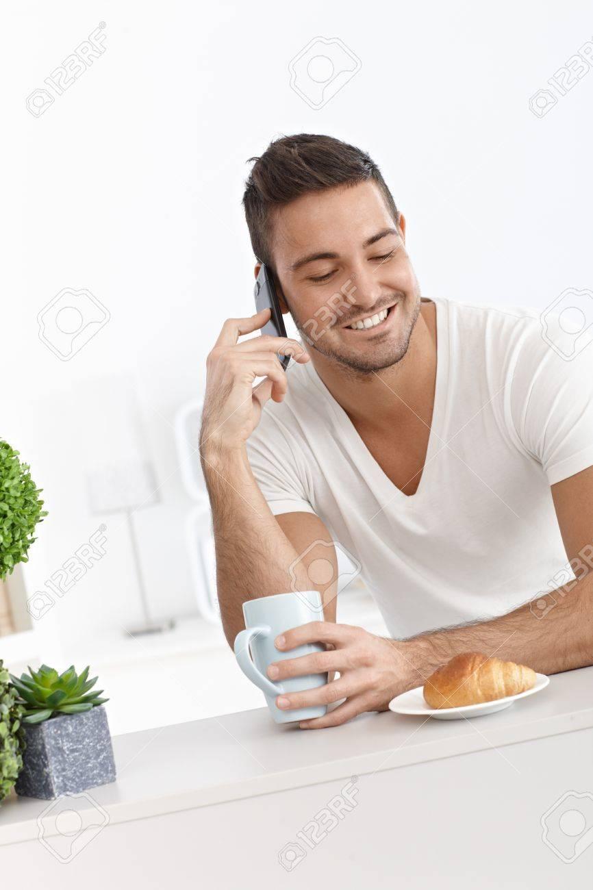 Happy man having breakfast, talking on mobile phone. Stock Photo - 15032799