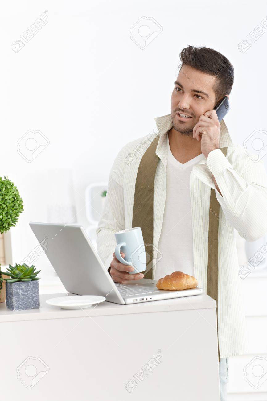 Young businessman talking on mobile, having breakfast, using laptop computer at home in the morning. Stock Photo - 15032791