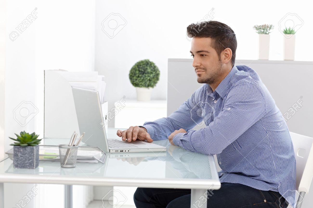 Young Man Using Laptop Computer Working At Home Stock Photo