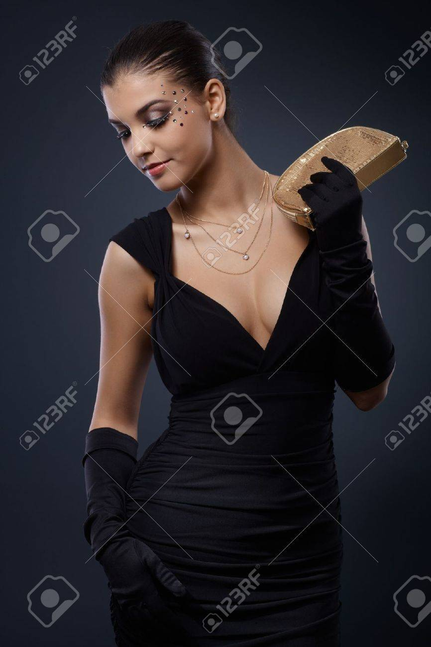 Attractive young woman with fancy rhinestones makeup posing in elegant evening dress with handbag. Stock Photo - 15033017