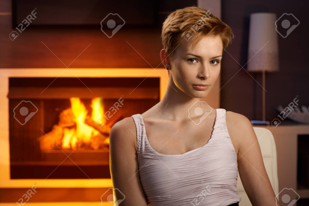 Attractive young woman sitting by fireplace at home, looking at camera. Stock Photo - 15100775