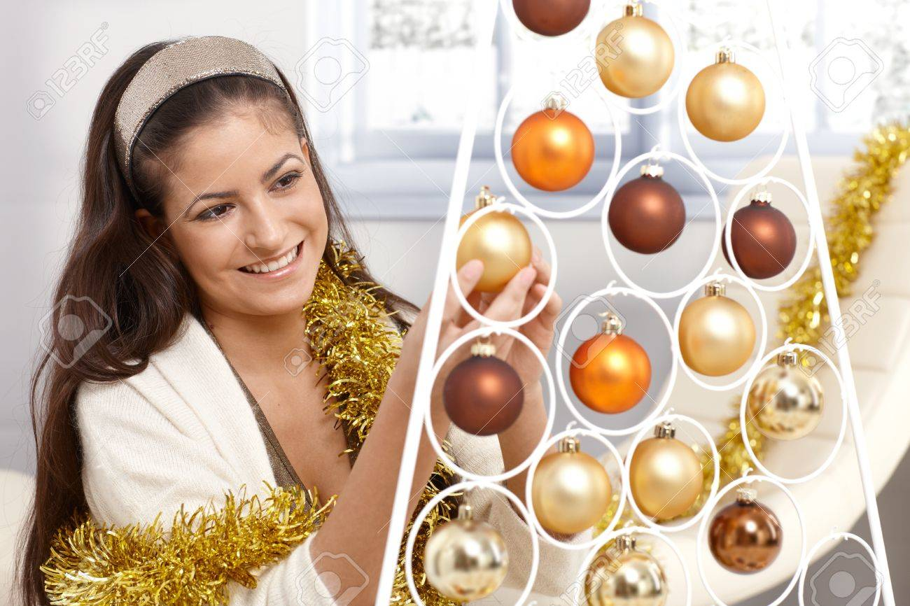 Smiling young woman getting ready for christmas, decorating with garland and bulb at home. Stock Photo - 15286974