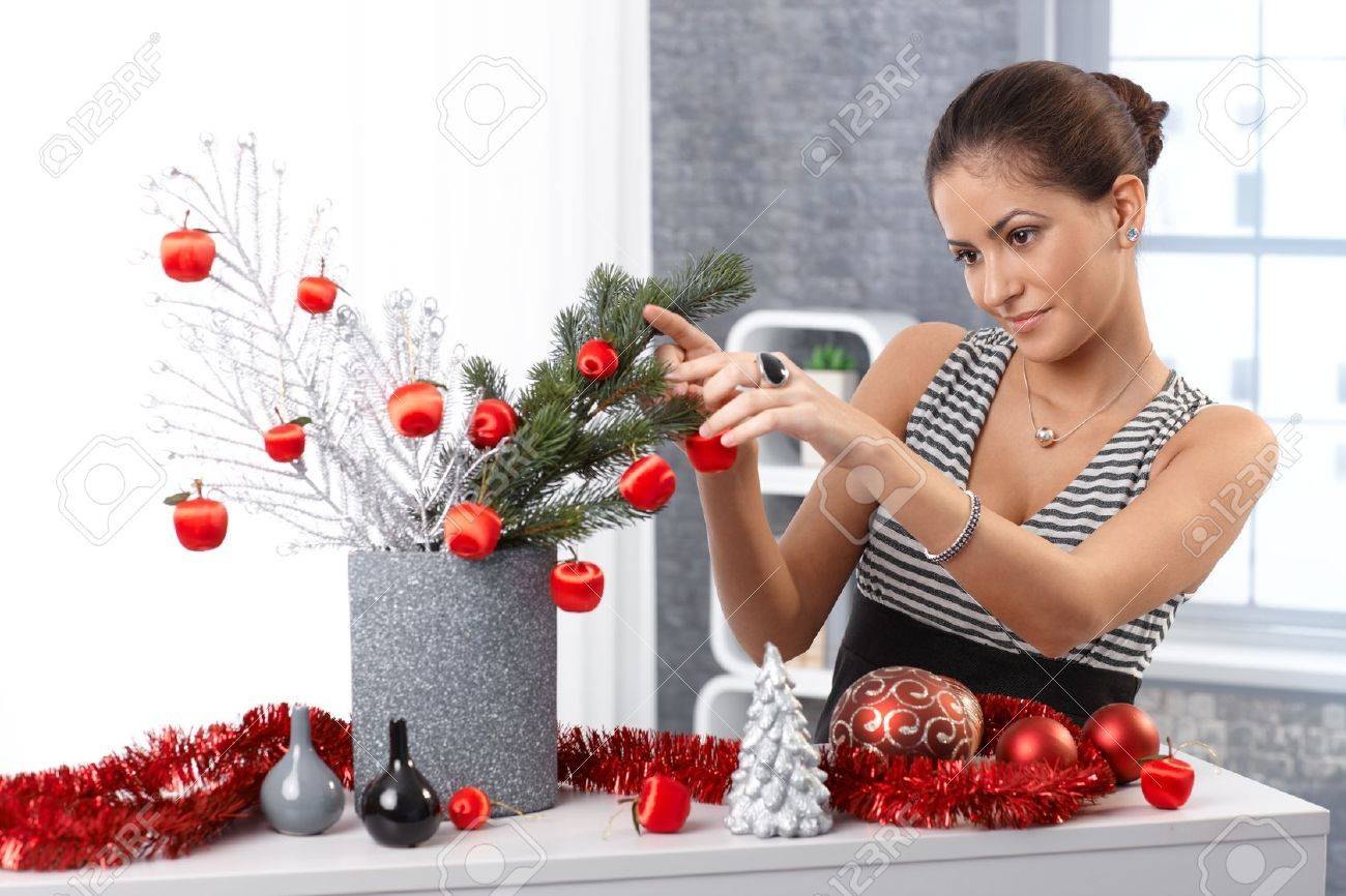 Portrait of young woman making christmas decoration at home, using stylish red bulb and garland, smiling. Stock Photo - 15286918