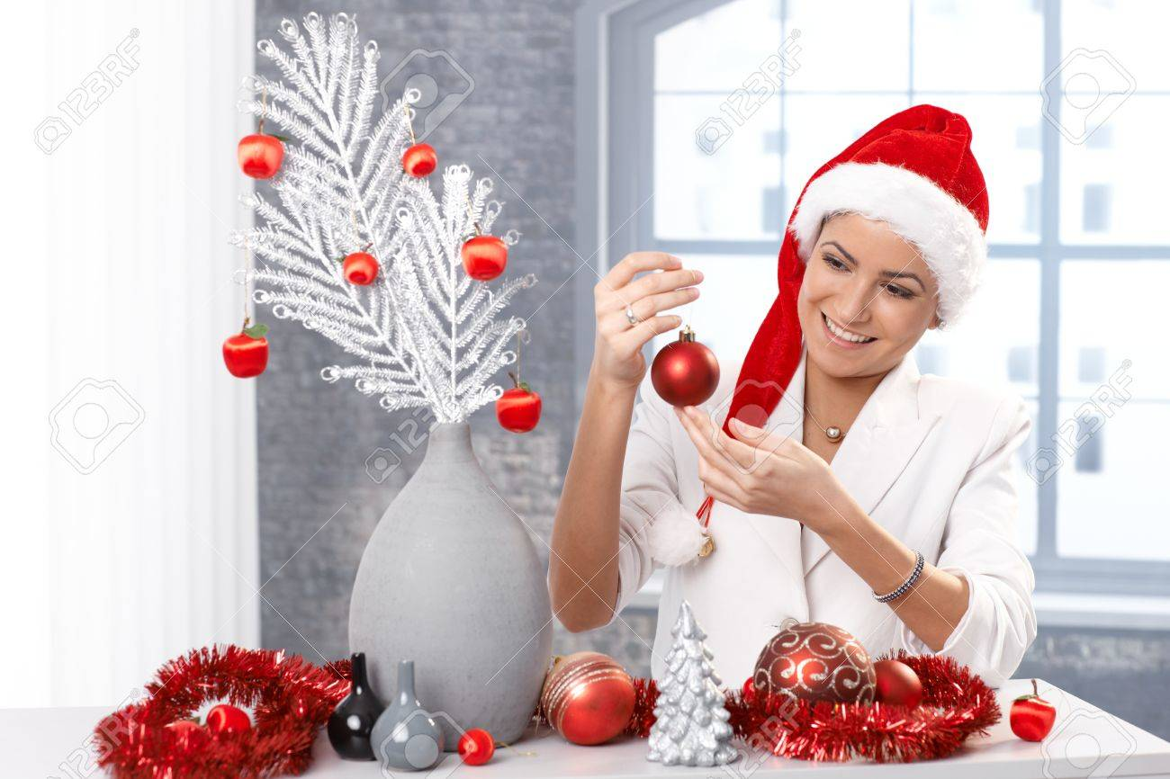 Woman Home Decorating happy woman getting ready for christmas, decorating home, wearing