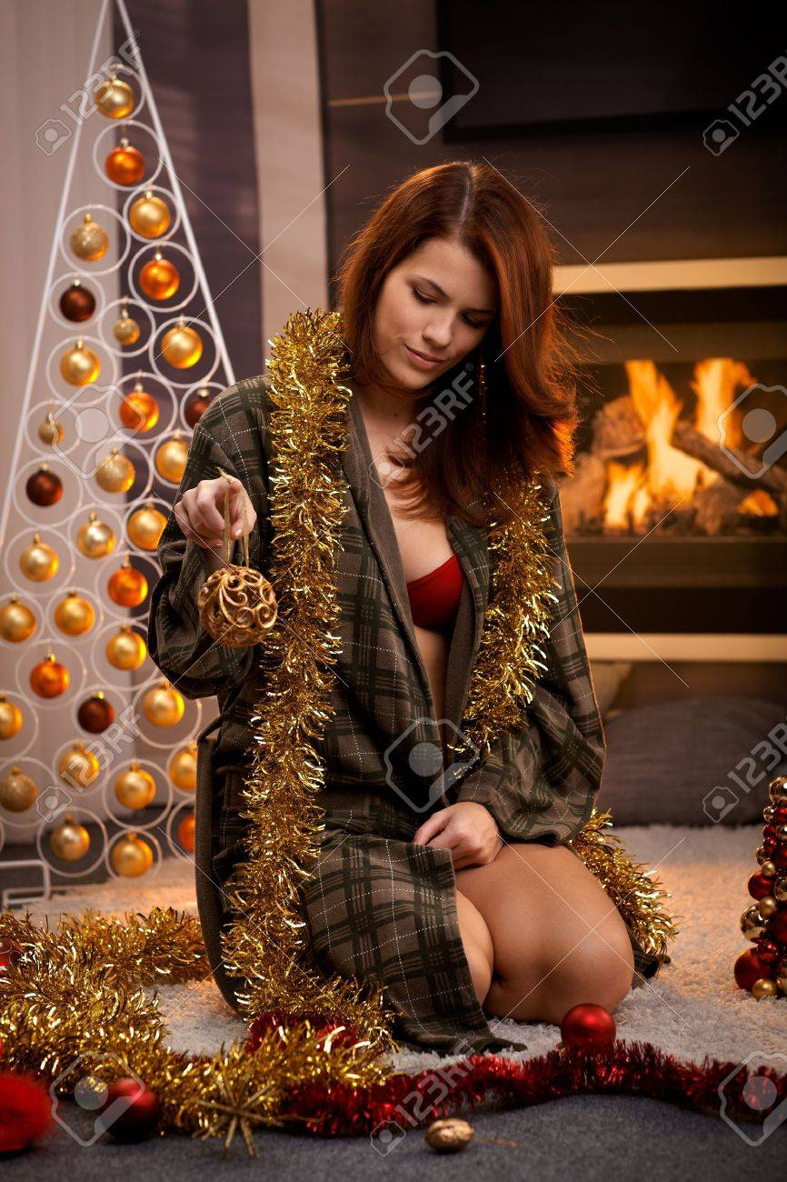 Sexy christmas portrait of attractive woman in dressing gown and red bra, decorating cosy living room for christmas. Stock Photo - 15287096