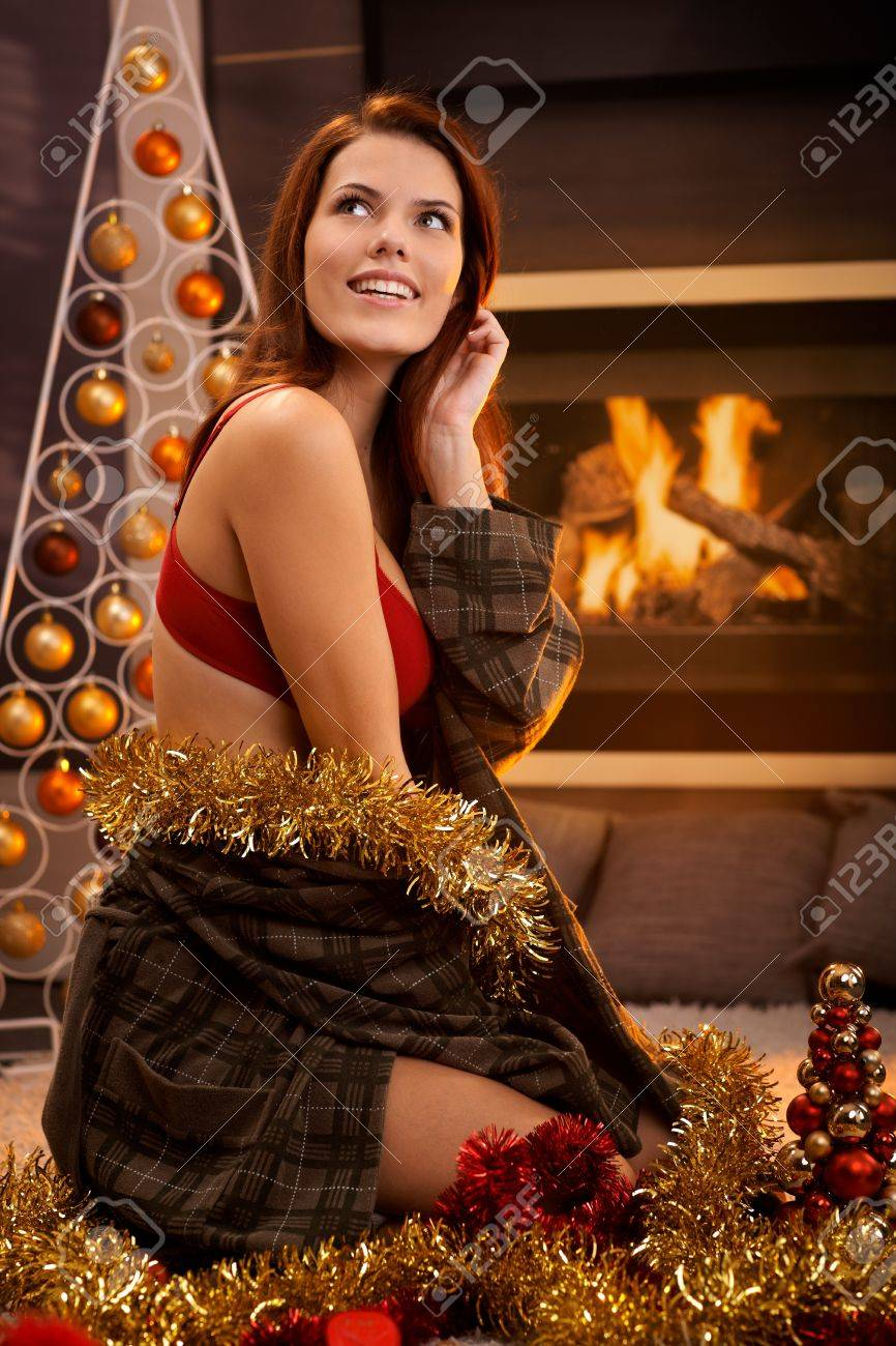 Portrait of hot girl smiling, posing in red bra and dressing gown surrounded with christmas decoration in front of cosy fireplace. Stock Photo - 15287093