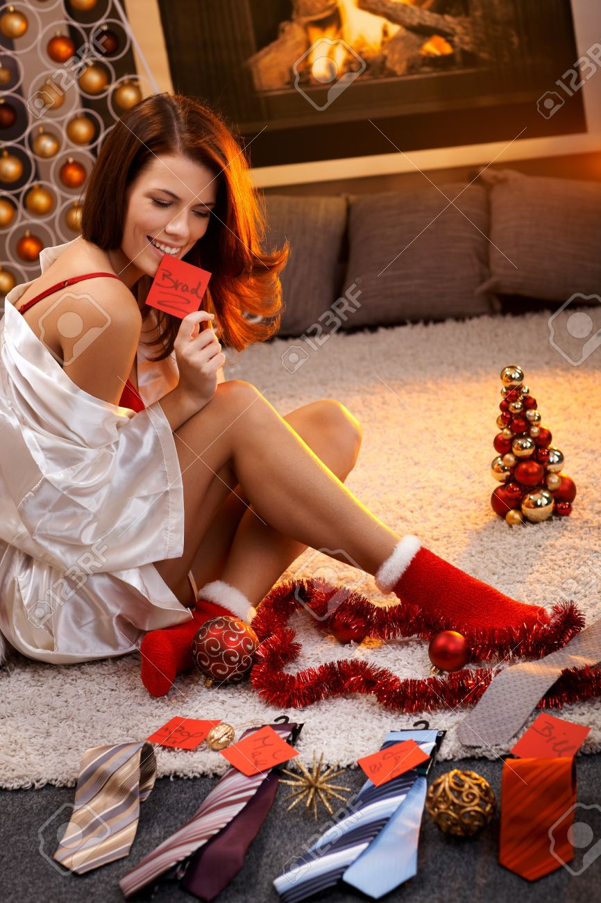 sexy woman in silk gown and christmas socks arranging christmas gifts tie with name tag