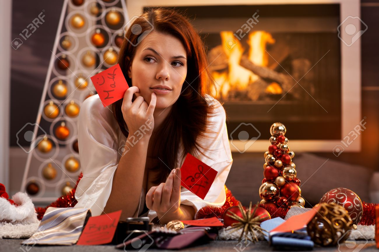 Woman arranging christmas gifts by fireplace, holding gift tag with male names, thinking, smiling, looking aside. Stock Photo - 15287053