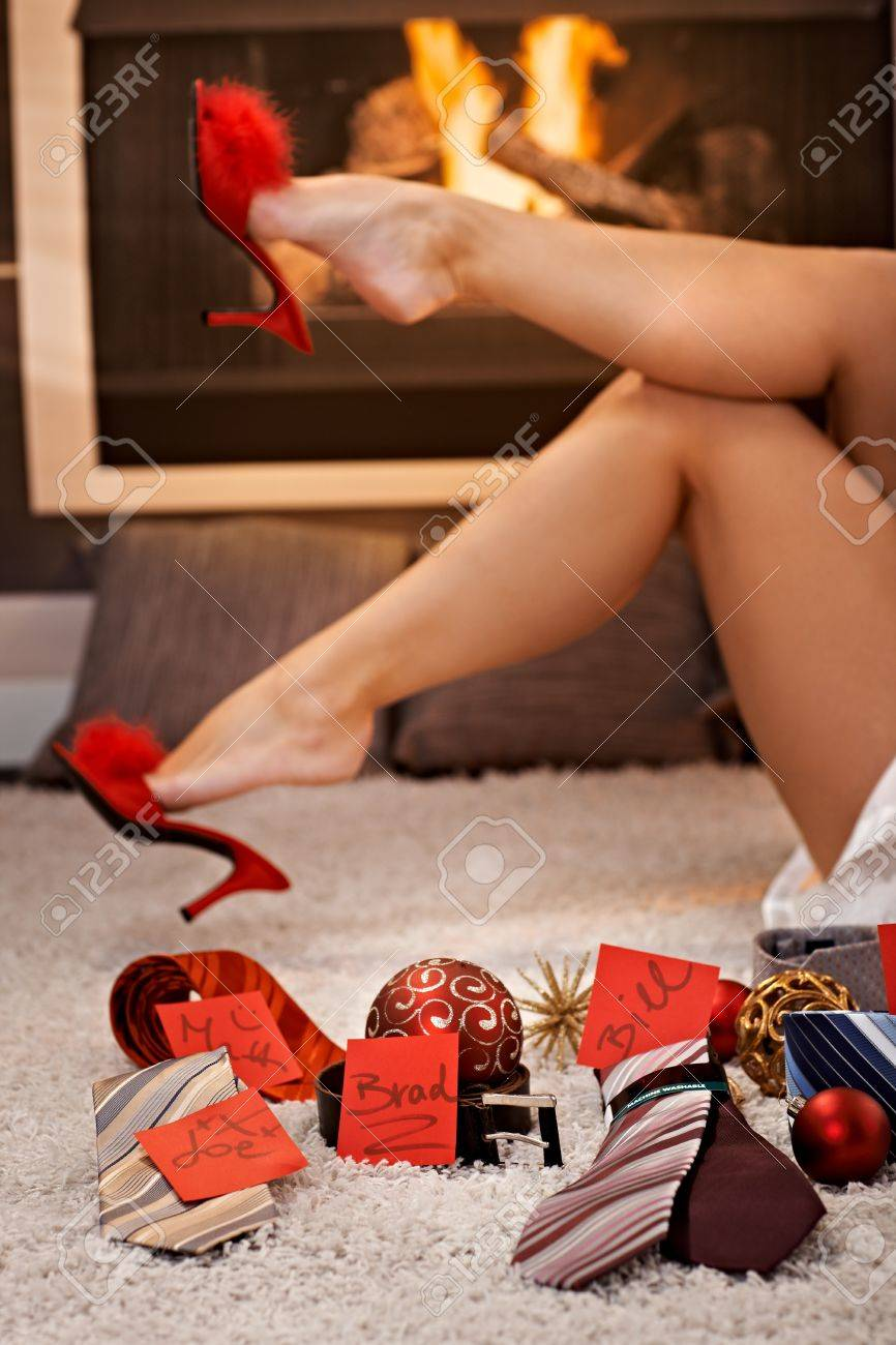 Pretty female legs in sexy red high heel slipper and christmas gifts of  tie, belt