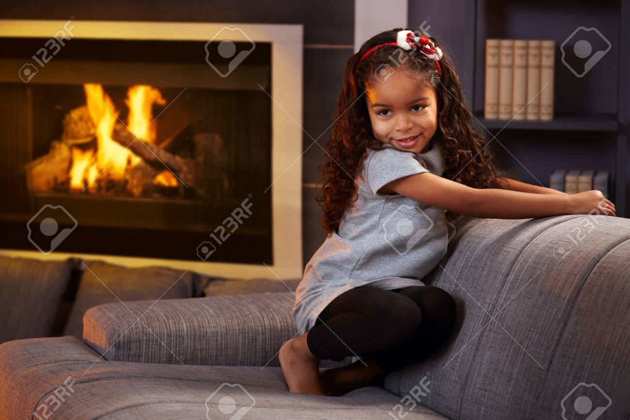 Beautiful afro little girl squatting on sofa in living room, smiling impishly. Stock Photo - 15287076