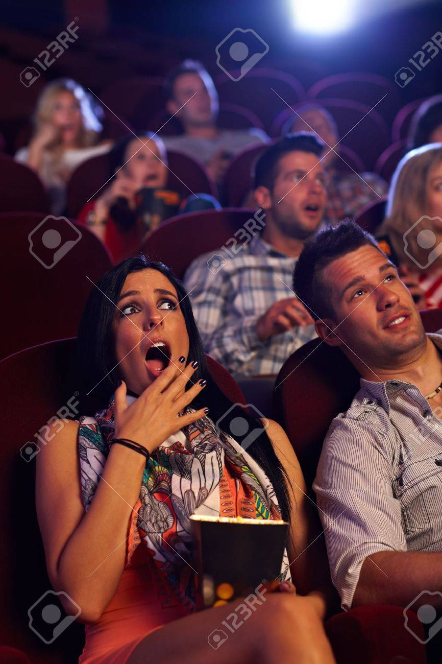 Young woman watching horror movie at cinema, looking shocked, holding popcorn in hand. Stock Photo - 15642382