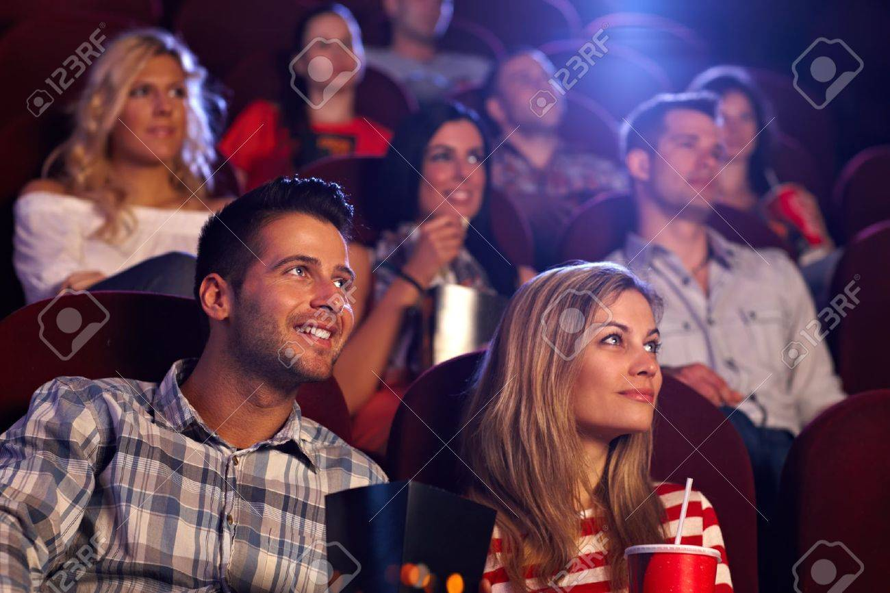 Young people sitting at auditorium of movie theater, watching movie. Stock Photo - 15642376