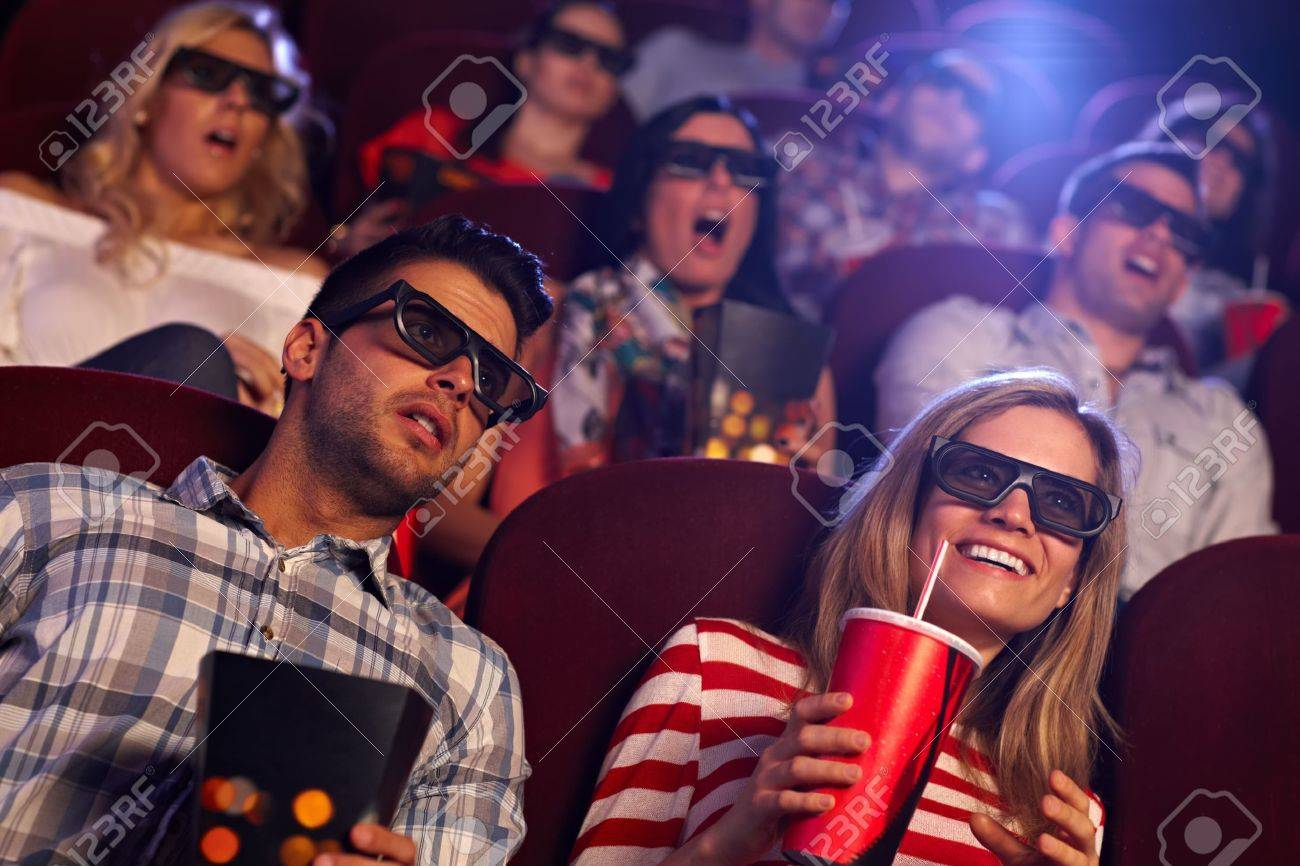 Young people sitting at cinema, watching 3D film, smiling. Stock Photo - 15642296