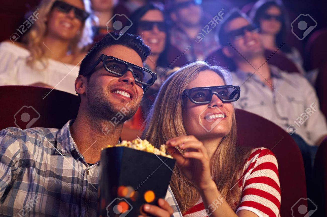 Happy couple sitting in movie theater, watching 3D movie, eating popcorn, smiling. Stock Photo - 15642304