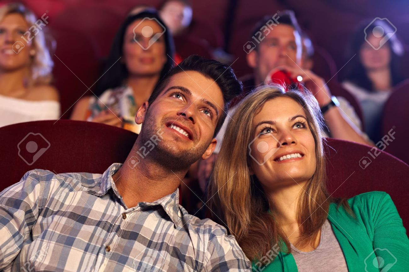 Happy young couple watching movie in cinema, smiling. Stock Photo - 15642318