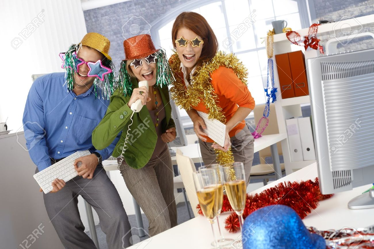 Funny new year eve party in office, businesspeople singing dancing with office tools, wearing festive party hat and glasses. Stock Photo - 15833410